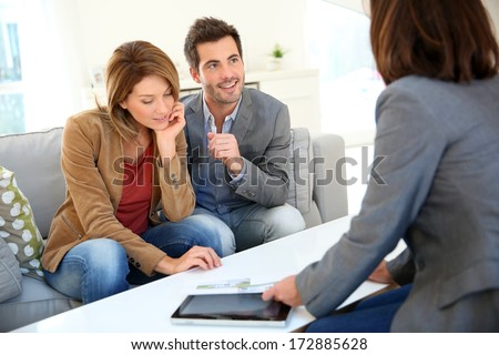 Couple meeting financial adviser for real estate project - stock photo