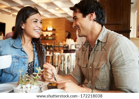 Couple Meeting In Busy Cafe Restaurant - stock photo