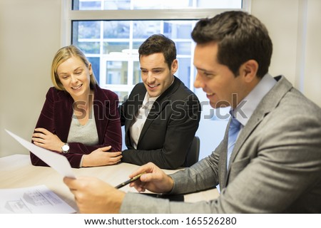 Couple meeting real-estate agent to buy property - stock photo