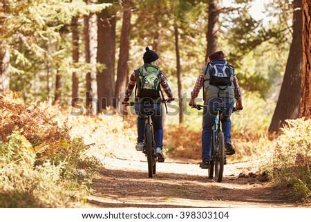 Couple mountain biking through forest, back view full length - stock photo