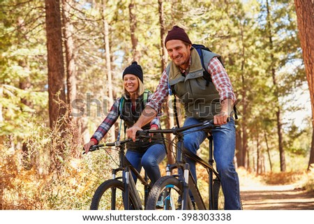 Couple mountain biking through forest, looking to camera