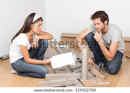 Couple moving in assembling bed furniture with problems and difficulties. Young interracial couple in new home. Asian woman, Caucasian man. - stock photo