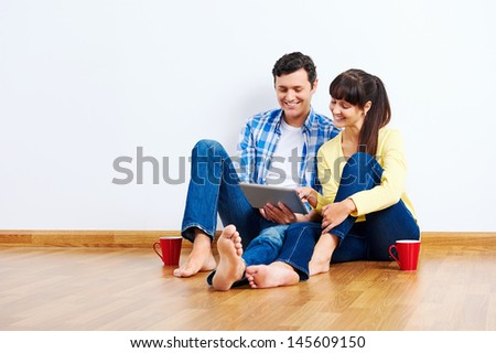 Couple moving in to new home and using wireless internet on tablet computer - stock photo