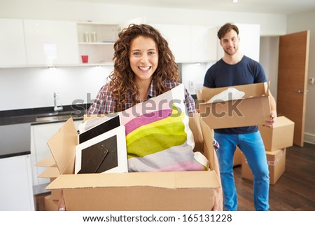 Couple Moving Into New Home And Unpacking Boxes - stock photo