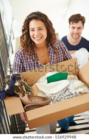 Couple Moving Into New Home Carrying Box Upstairs - stock photo