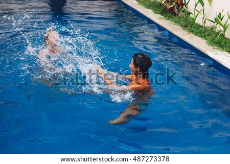 Couple multiracial girl friends  having fun in the swimming pool during holiday vacation in paradise island in Asia