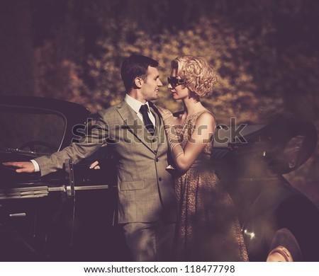 Couple near a retro car outdoors - stock photo