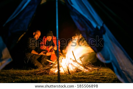 Couple near camp fire warming up seen from the tent - stock photo