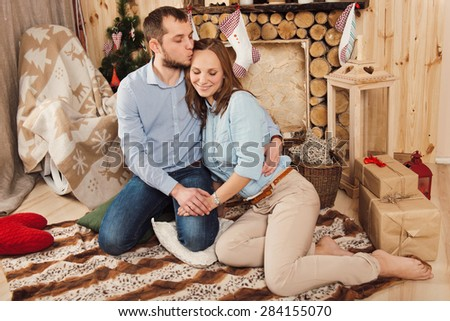 Couple near fireplace in Christmas decorated house interior. They hugging each other and holding hands.  - stock photo