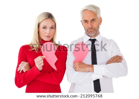 Couple not talking holding two halves of broken heart on white background - stock photo