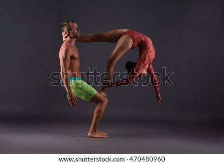 Couple of acrobats performing trick in studio