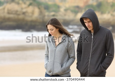 Couple of angry and sad teenagers together walking on the beach - stock photo