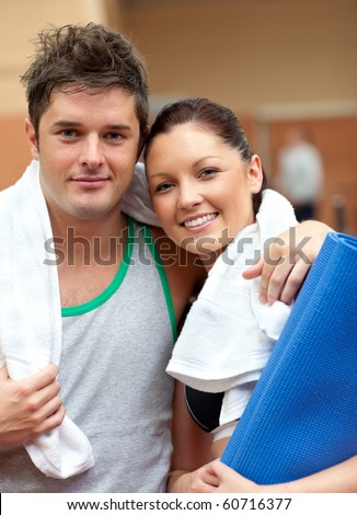 Couple of athletic people smiling at the camera in a fitness center - stock photo