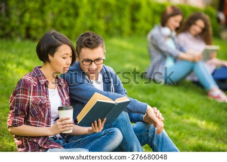 Couple of attractive smiling students dressed casual  studying outdoors on campus at the university. - stock photo