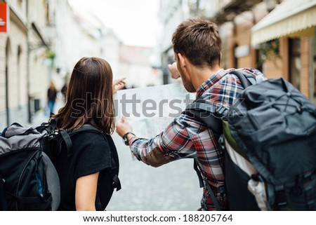 Couple of backpackers looking at city map  - stock photo