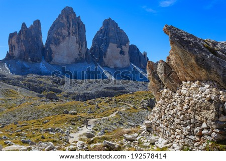 Couple of backpackers on hiking path with view of Tre Cime di Lavaredo famous rock formation, Dolomites Mountains, Italy  - stock photo