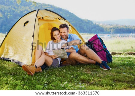 Couple of backpackers sitting outside the tent and reading map - stock photo