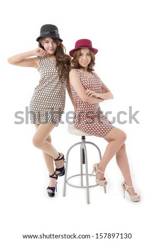 Couple of beautiful asian woman posing in plaid dress isolated on white background.