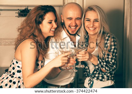 couple of beautiful ladies having fun with a guy at a party with a glass of martini. Celebrate, disco, party, nightlife, entertainment, friendship concept. - stock photo