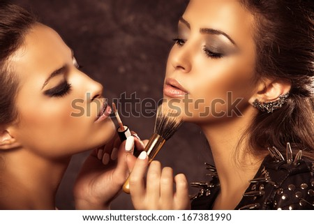 couple of beautiful two women make up each other, golden colors, studio shot