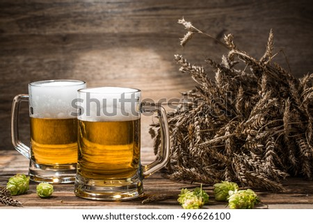 Couple of beers on table with hop and wheat in empty wooden background