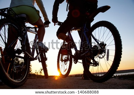 Couple of bicyclists on the brink of  rock looks at sunset