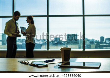 Couple of business man, woman talk about document Object tool in office room tablet computer paper cup with hot coffee Cell mobile phone Paper document lie on table against blue sky window with houses - stock photo