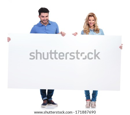 couple of casual people presenting a big blank billboard on white background - stock photo