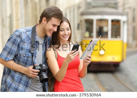Couple of casual tourists consulting a paper guide and gps in a smartphone on line in the street of an old town - stock photo