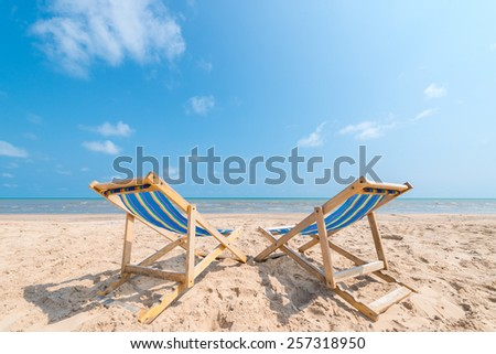 Couple of chairs on sandy beach on sunny day looking for the blue sea, relaxation concept - stock photo