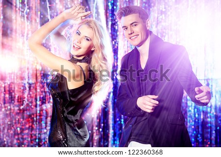 Couple of cheerful young people dancing at a party.