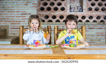 Couple of children sitting at a table eating breakfast pastries and chocolate and playing