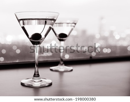 Couple of cocktail glasses with city view. - stock photo
