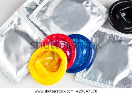 Couple of Colorful condoms with packaging, isolated on white background - stock photo