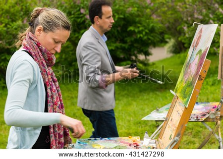 Couple of concentrated artists in a process of  working  on a trestle and easel painting with oils and acrylics during an art class in a park