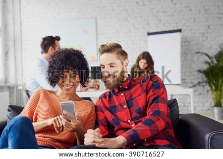 Couple of coworkers, students sharing together smartphone, sitting at creative office on couch
