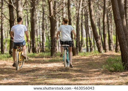 couple of cyclists riding bicycles on sunny summer day