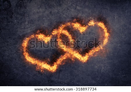Couple of decorative overlapping flaming hearts with fiery orange flames for valentines day or a wedding, symbolic of love and romance, dark background with copyspace - stock photo