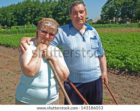 Couple of elderly country farmers with gardening tools