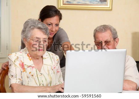 Couple of elderly persons with young woman using internet - stock photo