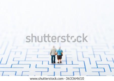 Couple of elderly walk through the maze - stock photo