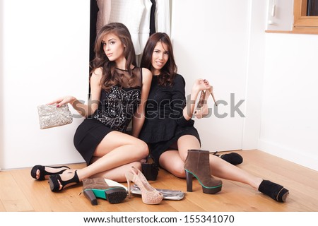 couple of elegant fashion girls sit in front of cupboard for clothes with their shoes around  - stock photo