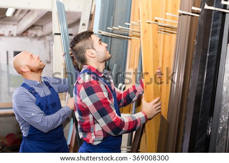 Couple of european workmen inspecting window frames at factory - stock photo