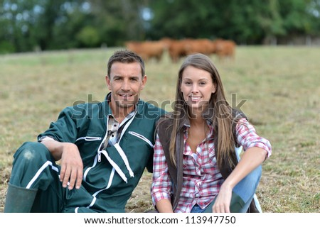 Couple of farmers sitting in field - stock photo