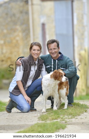 Couple of farmers with dogs around farm house - stock photo