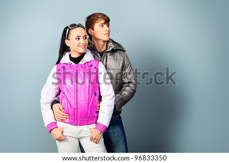 Couple of fashion models in winter, spring clothes posing at the studio.