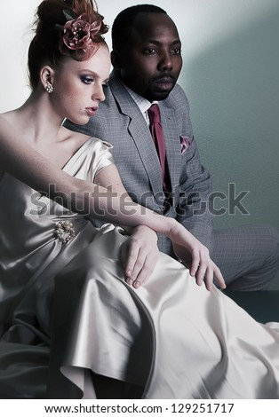 Couple of fashion models sitting - stylish black american man and redhead fashionable woman