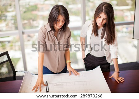 Couple of female business partners analyzing a project together in a meeting room with a view - stock photo