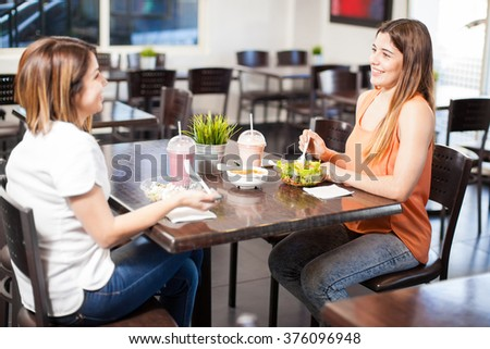 Couple of female friends having lunch together in a restaurant - stock photo
