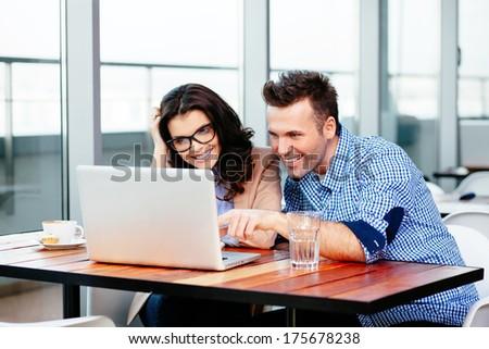 Couple of freelancers enjoying some online things - stock photo